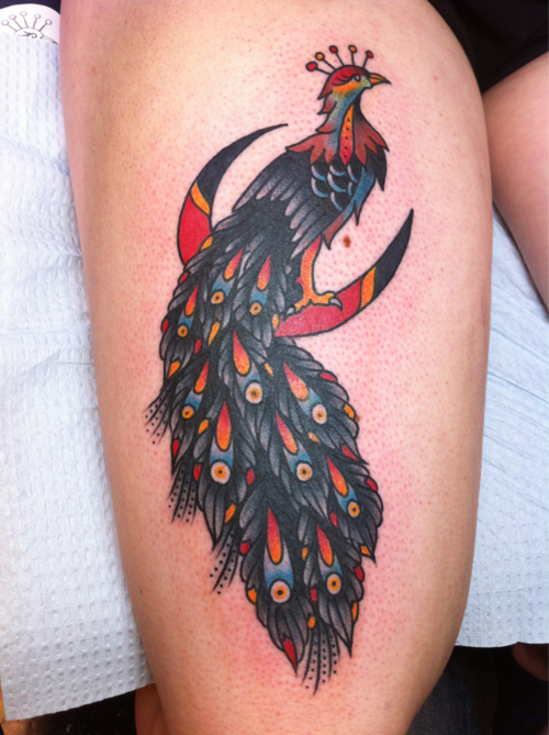 Small peacock tattoo on thigh