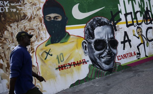 A man walks in front of mural covered in graffiti featuring Brazil's Neymar which has been modified to make the Barcelona striker look like a member of the Black Blocs, which have been active in Brazil's ongoing protest movement against the World Cup, in Rio de Janeiro, Brazil, Tuesday, May 27, 2014. Teams from 32 nations will compete in the upcoming World Cup, with Sao Paulo hosting the opening ceremony and kick-off match between Brazil and Croatia on June 12. (AP Photo/Hassan Ammar)